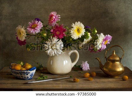 Still life with asters and yellow plums - stock photo