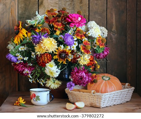 Still life with autumn bouquet of garden flowers and pumpkin on the background boards. - stock photo