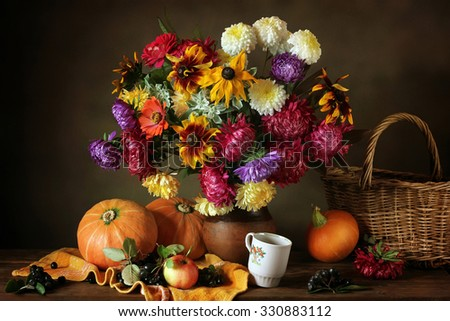 Still life with autumn flowers, berries, apple and pumpkins against a dark background. Asters and chrysanthemums. - stock photo