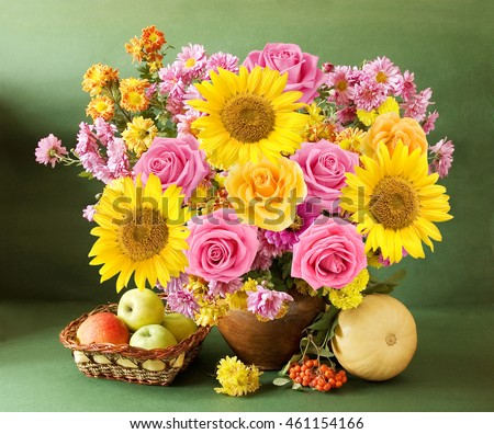 Still life with autumn flowers, sunflowers and roses, apples, rowan and gourd on artistic background