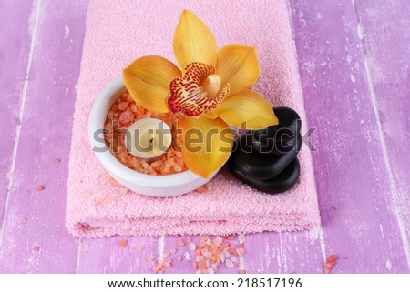 Still life with beautiful blooming orchid flower, towel and sea salt in bowl on color wooden background - stock photo