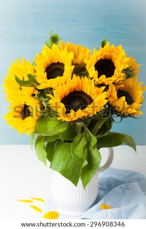 Still life with beautiful sunflowers bouquet in white vase on blue wooden background. Greeting card concept. - stock photo