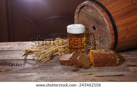 Still-life with beer, a wooden butt, and rye bread on a wooden table
