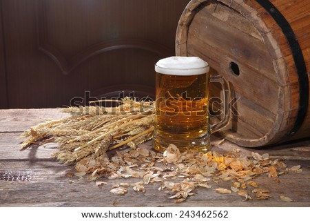 Still-life with beer, cones, hop and a butt on a wooden table
