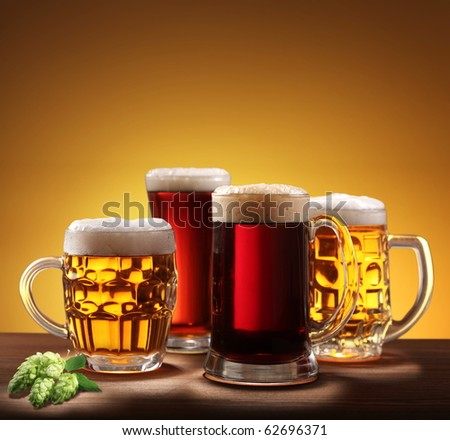 Still-life with beer glasses. On a yellow background. - stock photo