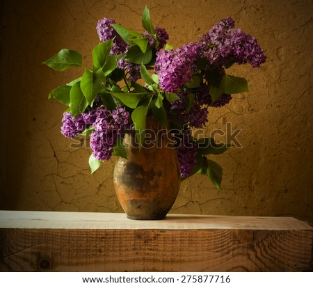 Still life with blooming branches of lilac in vases - stock photo