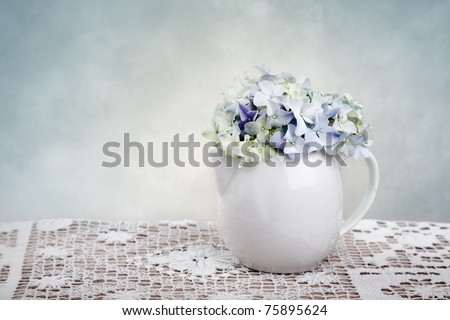 Still-Life with blue Hortensia Flowers in porcelaine can - stock photo