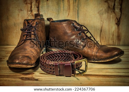 still life with boots and belt on table over wooden background