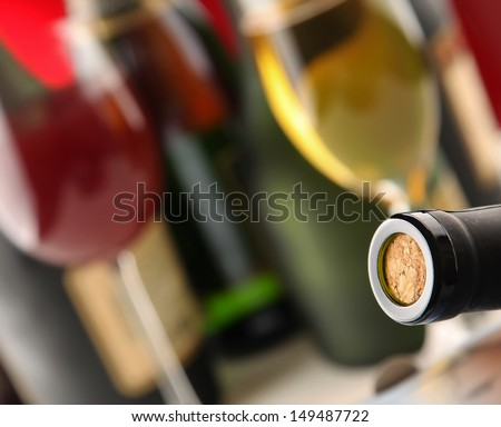 Still life with bottles, glasses, focus on a bottle with a cork - stock photo