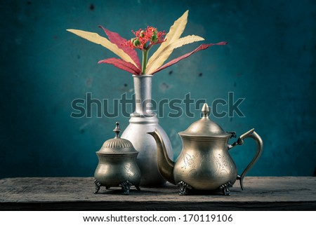 Still life with brass tea set and silver vase with colorful flowers - stock photo