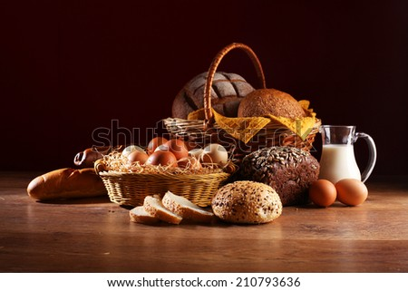 Still life with bread in basket and jug of milk - stock photo