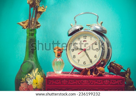 Still life with broken alarm clock, old glass vase with dead rose, perfume, vintage box - stock photo