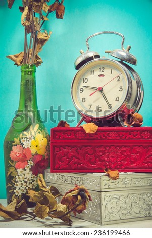 Still life with broken alarm clock, old glass vase with dead rose, vintage boxes, tone image. - stock photo