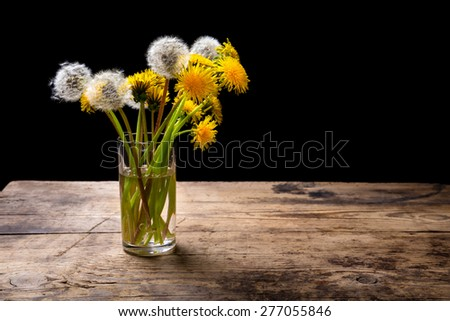 Still life with bunch of dandelions in glass on brown wood table with empty space for text - stock photo