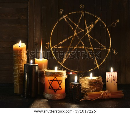 Still life with burning candles against pentagram circle background. Black magic ritual with occult, evil and esoteric symbols. Halloween or divination rite - stock photo