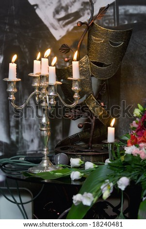 Still-life with candles, smiling mask and microphone