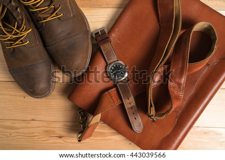 Still life with casual man, boots and bag on wooden table
