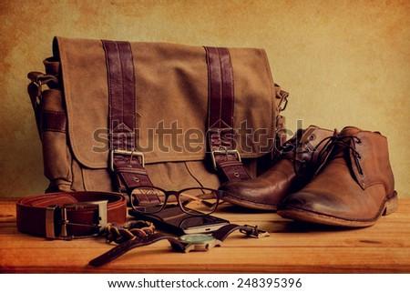 Still life with casual man, boots and bag on wooden table over grunge background - stock photo