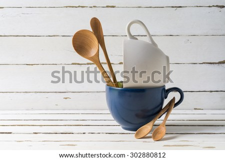 Still life with ceramic cup and wooden spoons on wooden table - stock photo