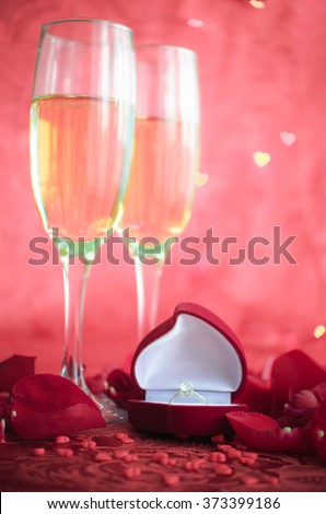 Still life with champagne, gift box and red rose petals on red background with bokeh in heart form. Marriage Proposal. Romantic Dinner: table place setting for Valentine's Day with diamond ring. - stock photo