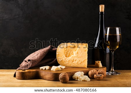 Still life with cheese and wine on a wooden board