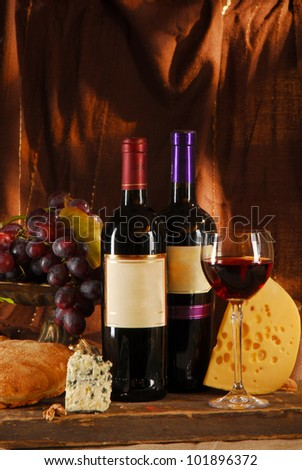 Still life with cheese, bread, grapes and two bottles of wine