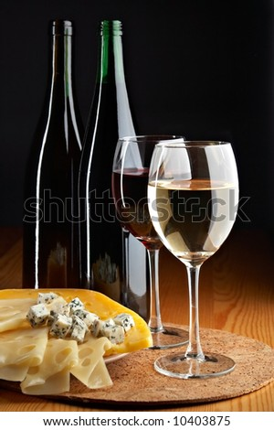 still life with cheese, red and white wines on the black background