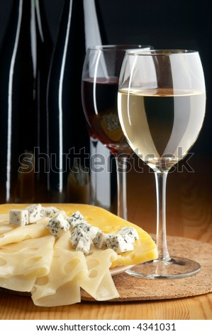 still life with cheeses, red and white wines on the black background
