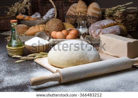 Still life with close-up of dough with all ingredients and pastry on the background