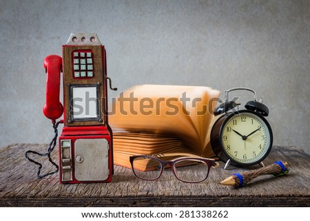 Still life with coin-operated phones,eyeglasses,book and clock on wooden table over grunge background - stock photo