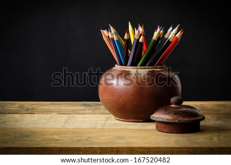 Still life with colour pencils in old clay jar on wooden table - stock photo
