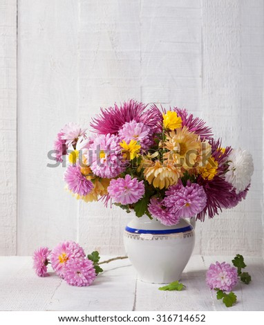 Still life with colourful chrysanthemums bunch on old white wooden board - stock photo