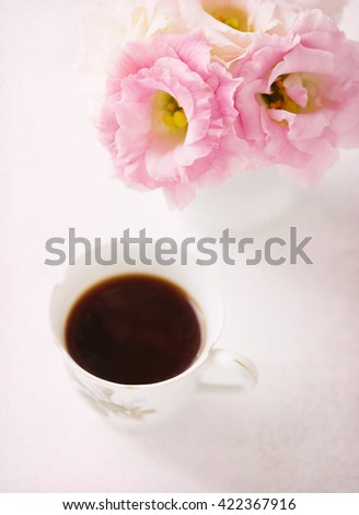 Still life with  cup of coffee  and flowers (Eustoma).  Selective focus. Shallow depth of field. Added paper texture - stock photo