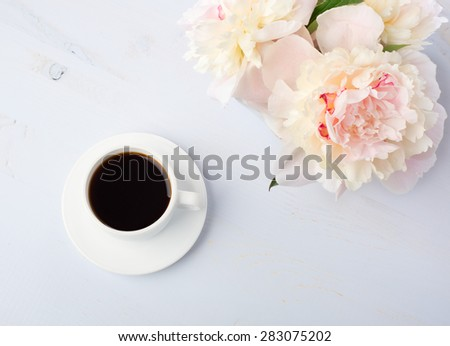 Still life with cup of coffee and flowers (peonies) on light blue wooden table. - stock photo
