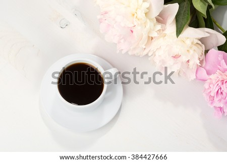 Still life with cup of coffee and flowers (peonies) on white wooden table.