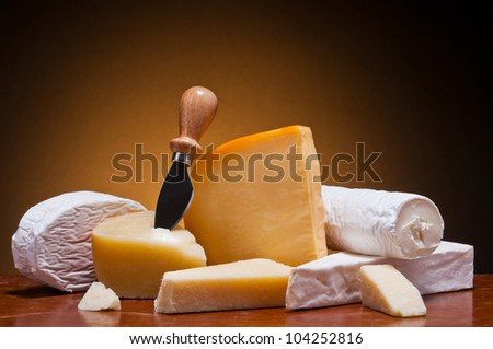 still life with different cheese on a wooden table - stock photo