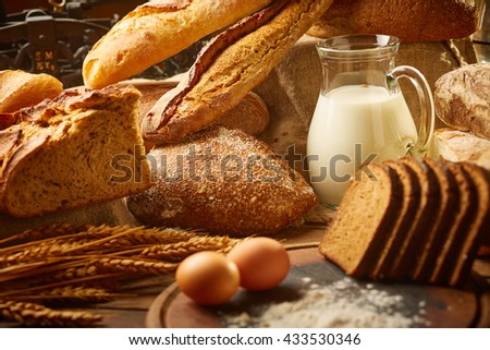 Still life with different kinds of bread, milk and eggs - stock photo