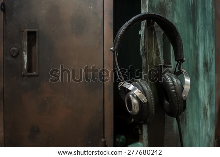 Still life with dramatic lighting image of headphone hang on the opened old high school locker  - stock photo