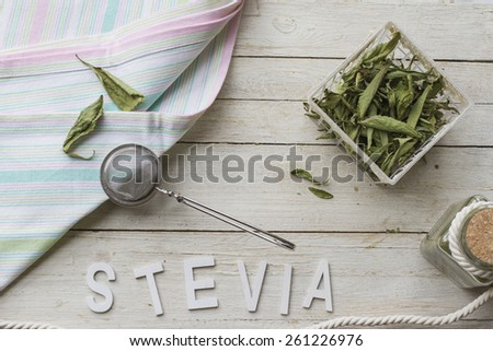 Still life with dried stevia leaves, sieve and cloth napkin, ready for making an infusion. - stock photo