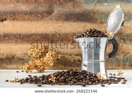 Still life with espresso pot, coffee beans with dry flower on wood table with steel plate  background - stock photo
