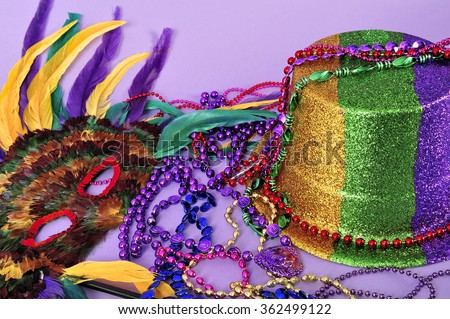 Still life with feathered mask, shiny party top hat, and beads on purple background. Objects symbolize Mardi Gras and also New Years, the opera, carnivals and the arts with copy space. - stock photo