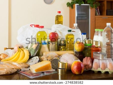 Still life with foodstuffs of supermarket on table in  interior - stock photo