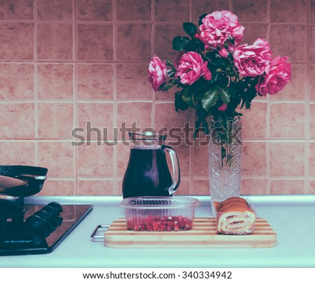 Still-life with fruit compote, pink roses, strawberry on kitchen table - stock photo
