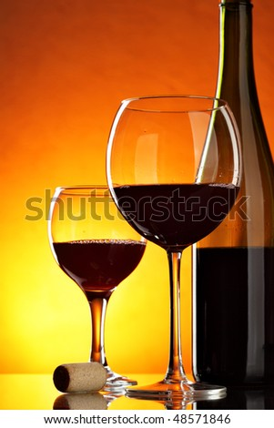 Still-life with glass and bottle of red wine on table - stock photo