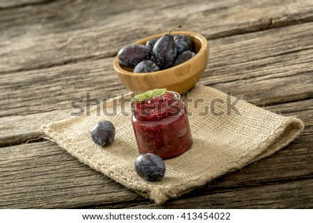 Still life with glass jar of fruit jam, wooden bowl full of ripe plums and two juicy plums lying on a linen table cloth on textured rustic wooden board. - stock photo