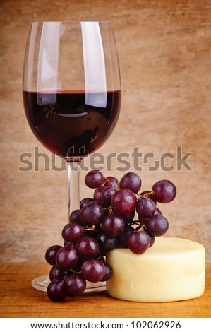 still life with glass of red wine, grapes and cheese on a wooden vintage background