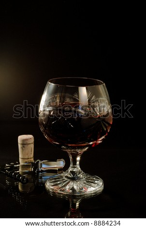 Still-life with glass of wine over black background