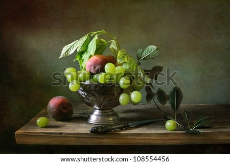 Still life with green grapes and peaches - stock photo