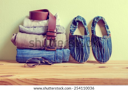 still life with handmade blue jeans shoes, t-shirt and pants on wooden table over grunge background, casual man - stock photo