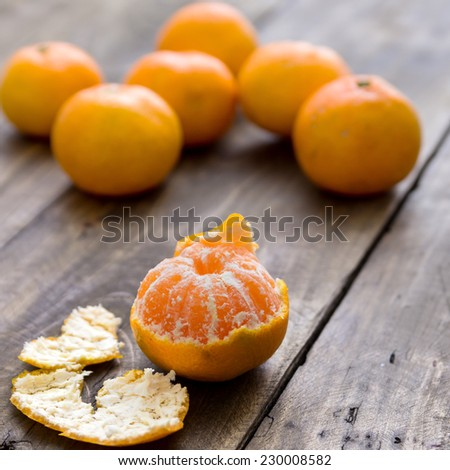 Still life with honey tangerines on antique wooden table - stock photo